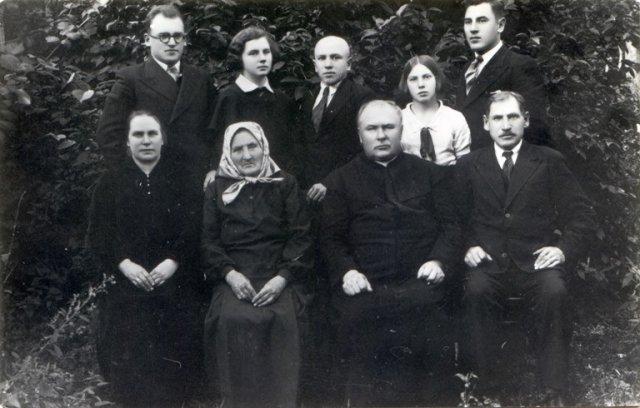B. Dundulis tėviškėje. Sėdi iš kairės: motina Paulina Dundulienė (Pukytė), senelė Domicelė Pukienė, dėdė kanauninkas (vėliau prelatas) Povilas Pukys, tėvas Jonas Dundulis. Stovi seserys ir broliai. (apie 1930-1932 m.)