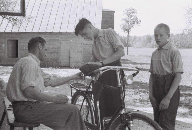 Dviračio taisymo procedūra Šileikiškyje. Stovi palinkęs prie dviračio Jonas Mažylis (Prano Mažylio sūnus, tuo metu gimnazistas, vėliau baigęs Kauno medicinos institutą ir jame dirbęs dėstytoju, Liudo Mažylio būsimas tėvas), šalia jo dešinėje - pusbro