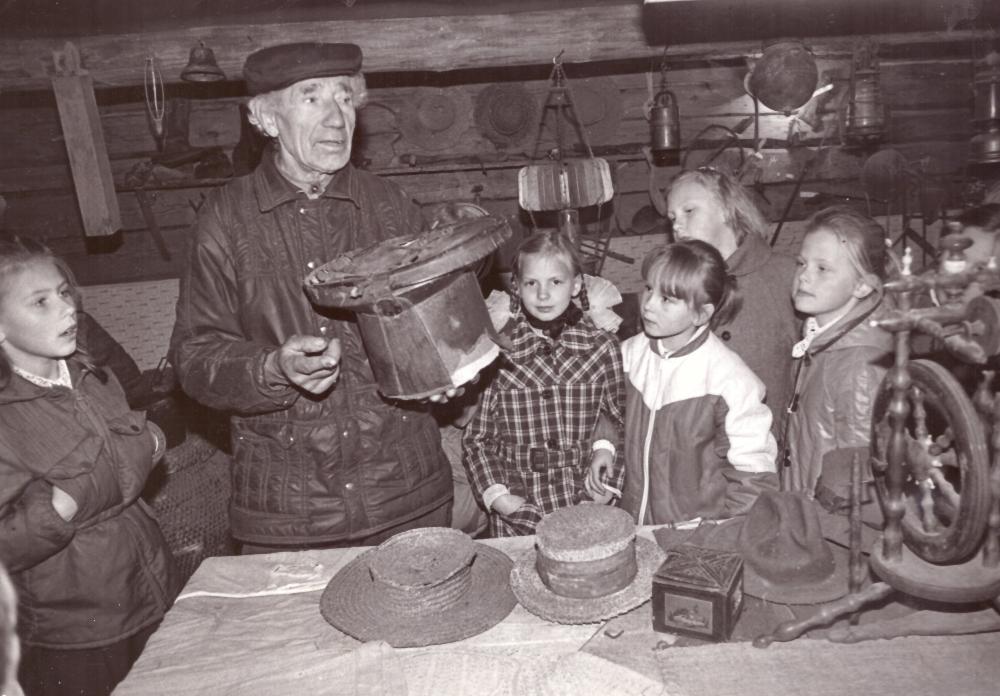 Adomas Petrauskas (antras iš kairės) su skrybėle rankose mažųjų lankytojų tarpe, klėties ekspozicijoje. GEK 833