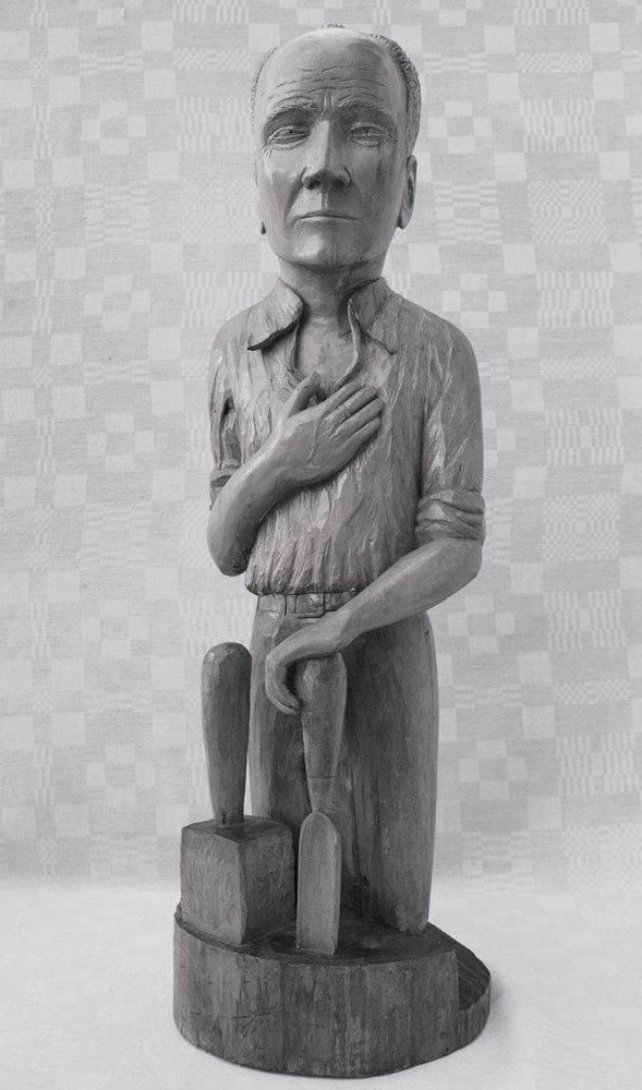 Skulptūra (medinė, 'Atleiskite', meistro autoportretas, vyras laiko rankose skaptuką, kitą prisidėjęs prie krūtinės, 1987 m., h - 72 cm.)