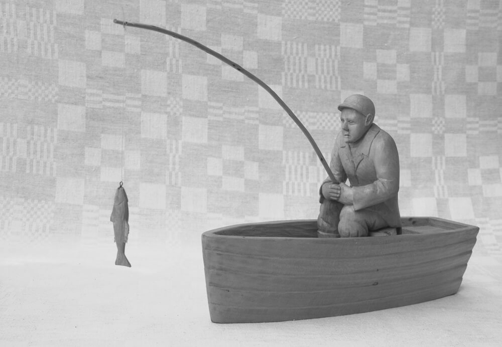Statulėlė (medinė, 'Žvejys', valtyje sėdi vyras su meškere, 2004 m., h - 20,5 cm., 31 x 6 cm.)