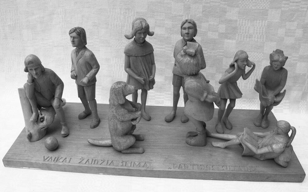 Kompozicija (medinė, ,Vaikai žaidžia šeimą', ant lentos įvairia veikla užsiimančių vaikų figūros, 1999 m.)