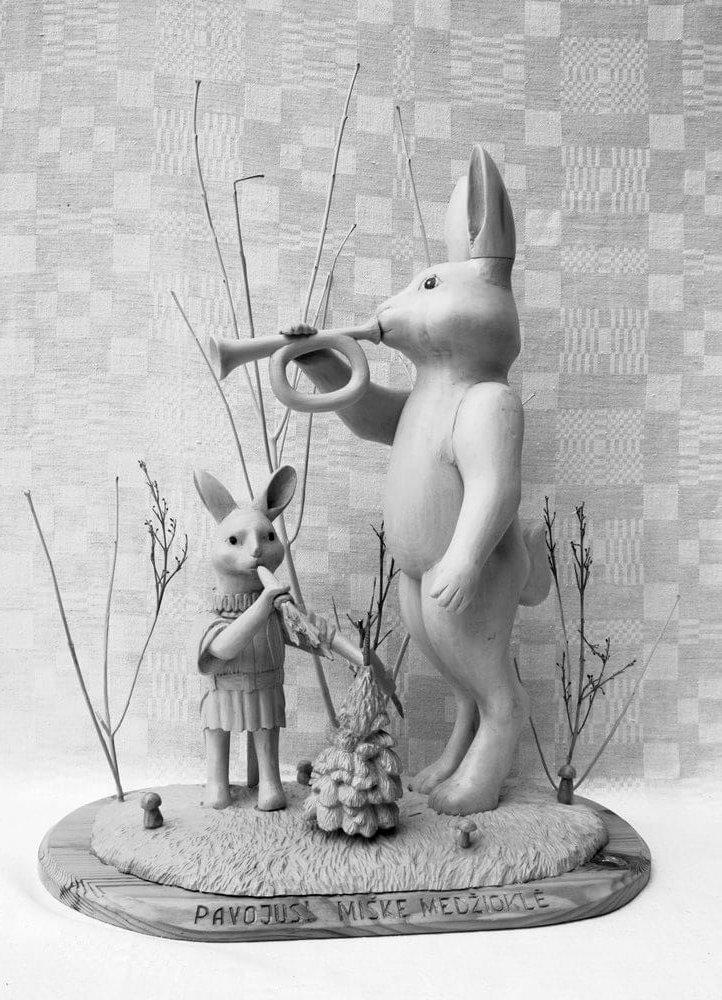 Kompozicija (medinė, ,Pavojus! Miške medžioklė', krūmynuose stovi du kiškiai, vienas jų pučia trimitą, 2013 m., 55,3 x 46,7 cm., h - 65 cm.)