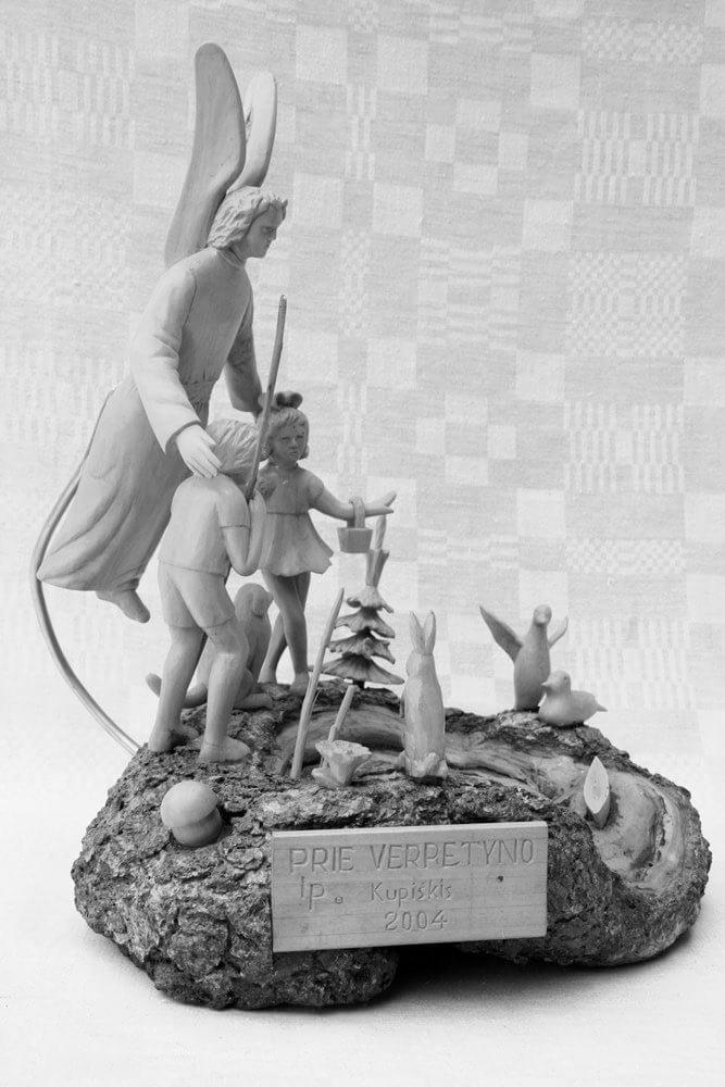 Kompozicija (medinė, ,Prie verpetyno', ant medžio gumbo, vaizduojančio verpetą, pritvirtintos įvairios figūrėlės, 2004 m., h - 39 cm.)