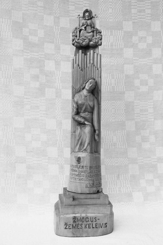 Statulėlė (medinė, ,Žmogus žemės keleivis', ant postamento moters figūra (sėdi), viršuje ant debesies - dievas, cituojamos B. Brazdžionio eilės, 1999 m., h - 59,9 cm.)